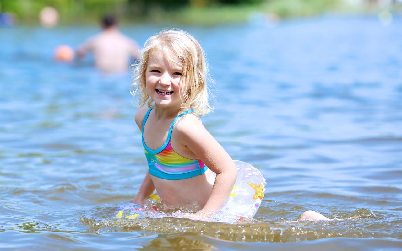 Kleines Maedchen freut mich im Wasser