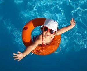 Kleines Maedchen mit Schwimmreifen im Hallenbad