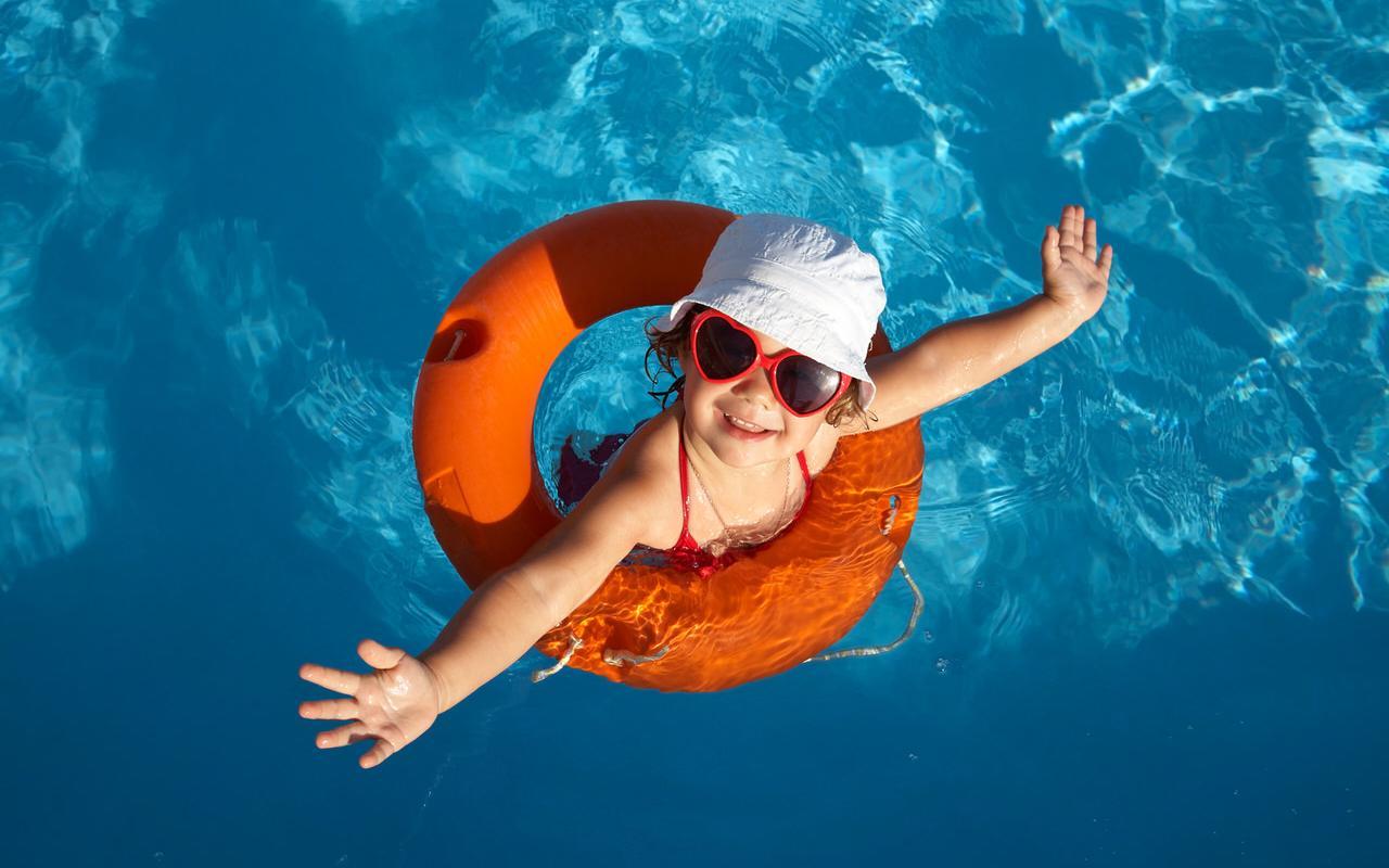 Little girl with swimming hoop in indoor pool
