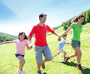 Family running across the meadow