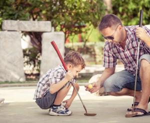 Vater und Sohn beim Minigolf spielen