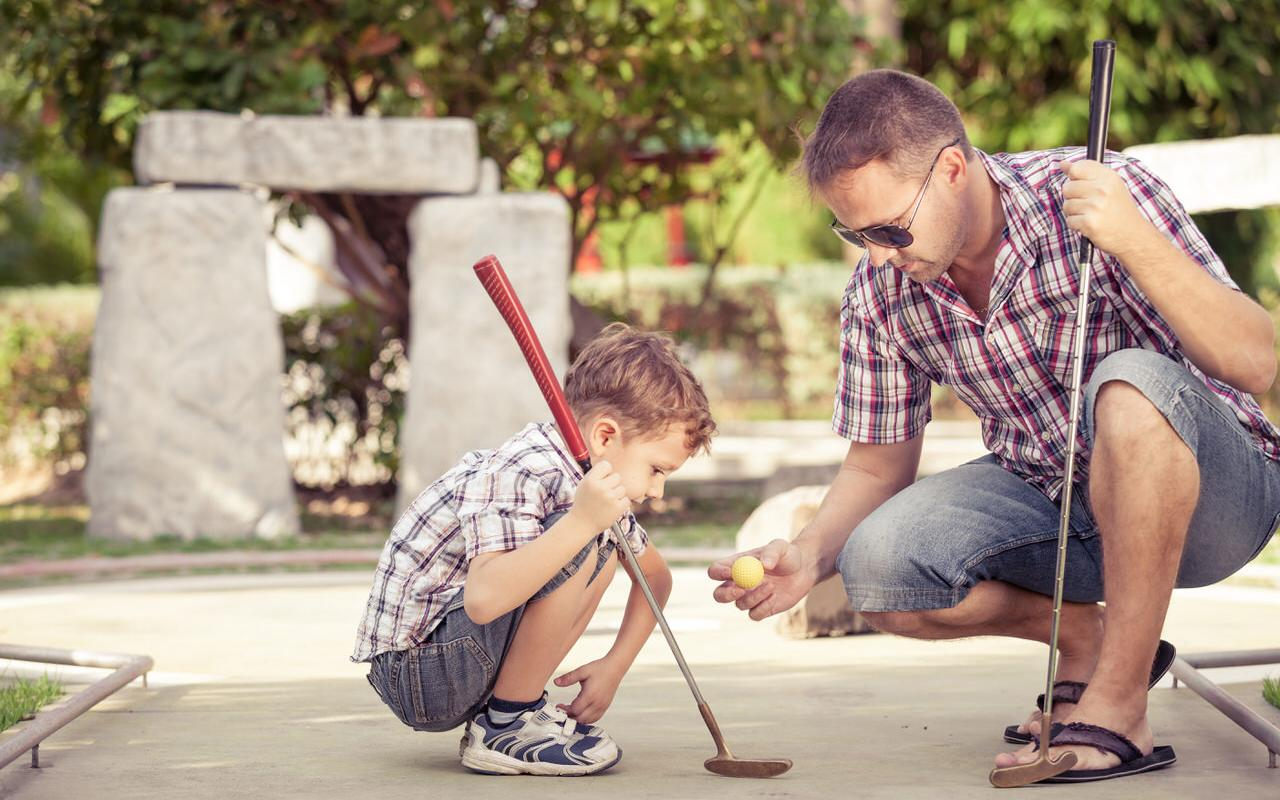 Father and son playing minigolf