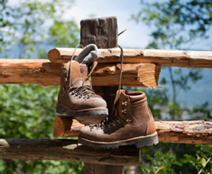 A pair of hiking boots hanging over a fence