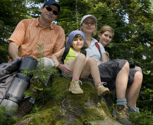 happy family resting on a stone while hiking
