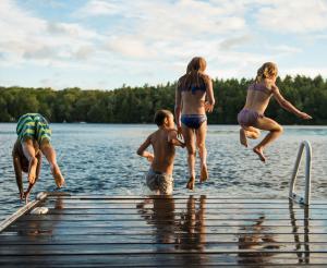 Eine Gruppe Jugendlicher springen in den Badesee