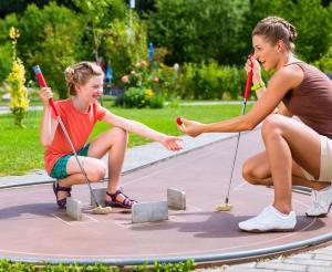 Mutter und Tochter spielen Minigolf