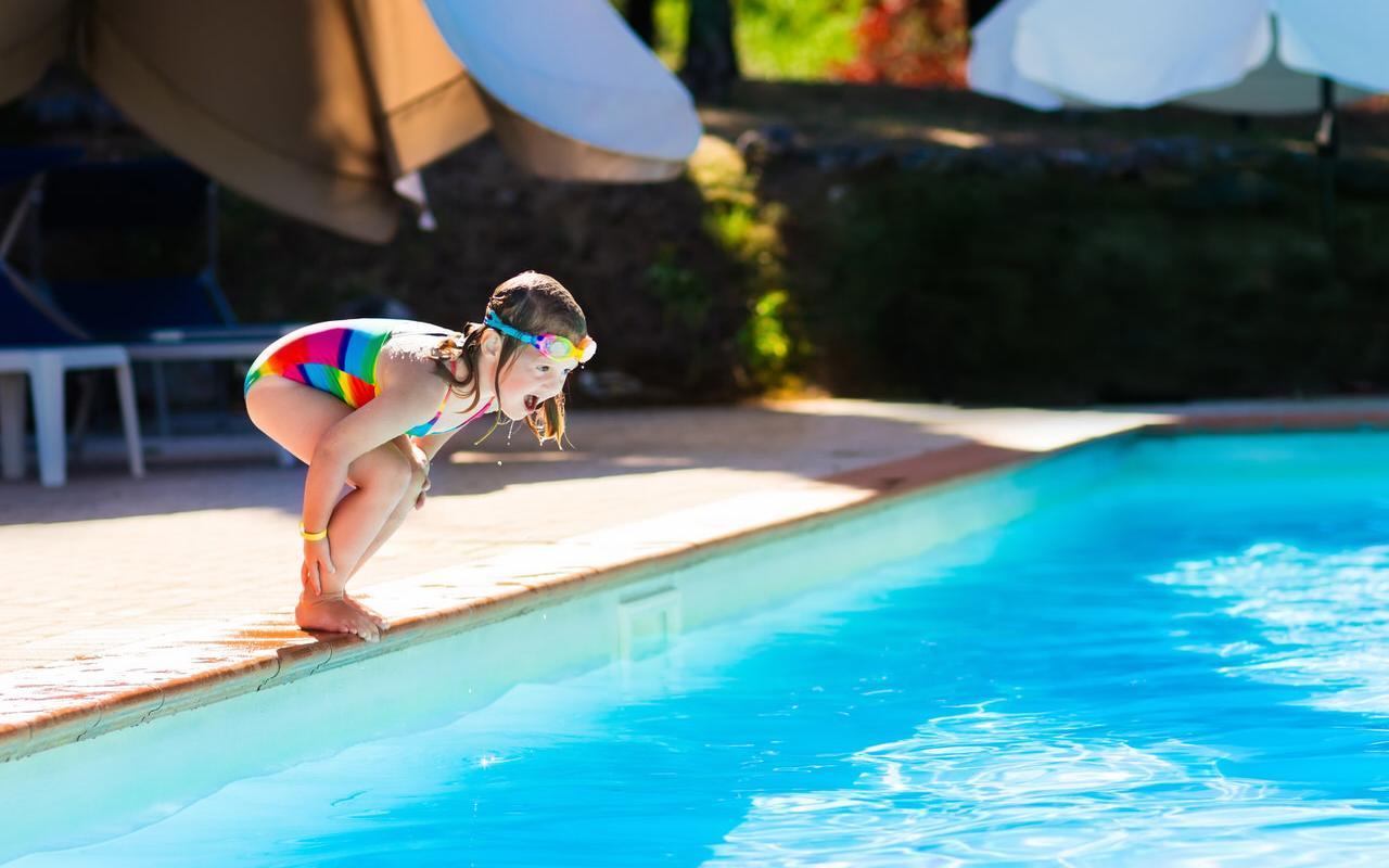 Kleines Maedchen vor Absprung ins Wasser