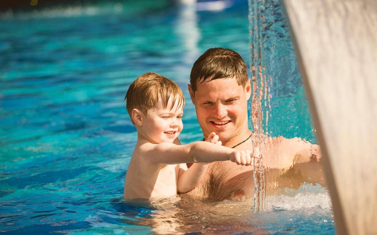 Vater mit Kind im Schwimmbad